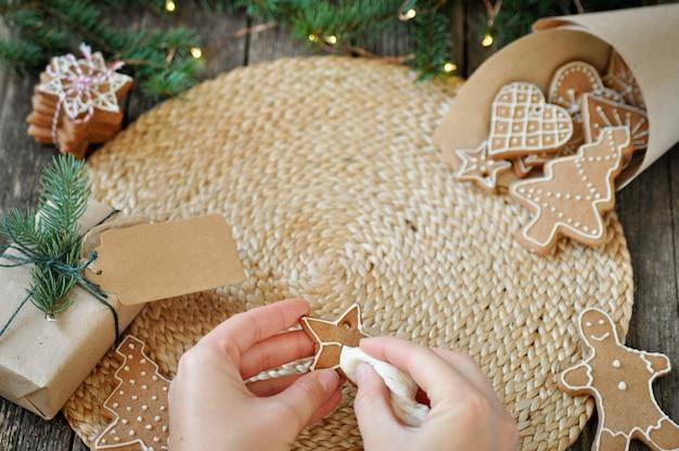 Die hände der frauen verzieren weihnachtslebkuchenplätzchen mit dem zucker, der auf schönem hölzernem bereift. Premium Fotos