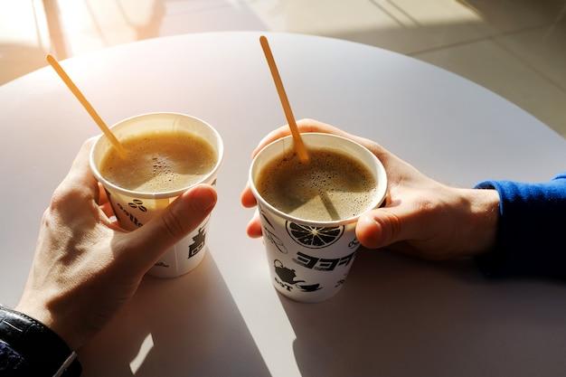Die hände der männer, die einen papierwegwerftasse kaffee auf einer weißen tabelle in einem café halten Premium Fotos