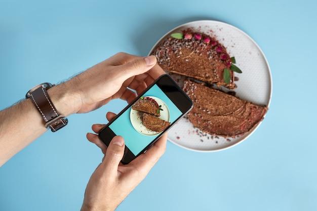 Die hände der männer machen ein foto von einem schokoladenkuchen auf ihrem smartphone auf einem blauen hintergrund. bloggen und essen fotos. Premium Fotos