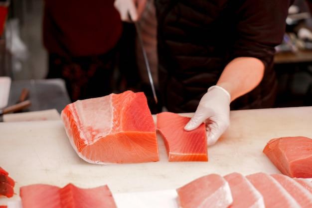 Die hände des japanischen chefs, der chefmesser verwendet, schnitten stück frische thunfische für verkauf an kunden im morgenfischmarkt, japan. Premium Fotos