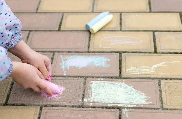 Die hände des kleinen mädchens zeichnen auf asphalt und pflastern steine mit bunter kreide. kinder spielen im freien Premium Fotos