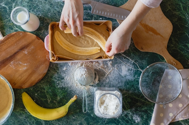 Die hände des mädchens geben geschnittene banane in den tortenteig. Premium Fotos
