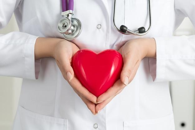 Die hände des weiblichen arztes halten rotes herz. nahaufnahmen der hände des doktors. medizinische hilfe, prophylaxe oder versicherungskonzept. Premium Fotos