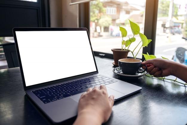 Die hände einer frau, die laptop mit leerem weißen desktop-bildschirm beim trinken von heißem kaffee auf holztisch im café verwendet Premium Fotos