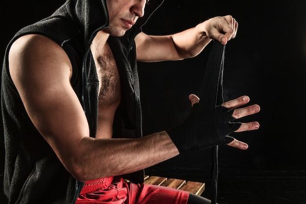 Die hände mit verband des muskulösen mannes trainieren kickboxen auf schwarz Kostenlose Fotos