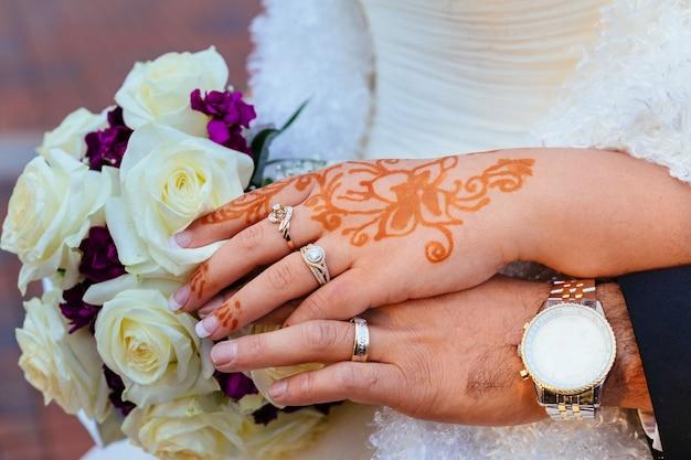 Die hand der braut mit hennastrauch-tätowierung und schmuck, hochzeit Premium Fotos