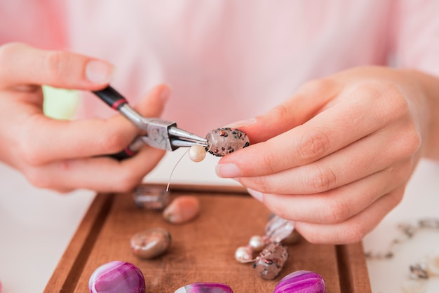 Die hand der frau, die das perlenarmband auf hölzernem behälter macht Kostenlose Fotos