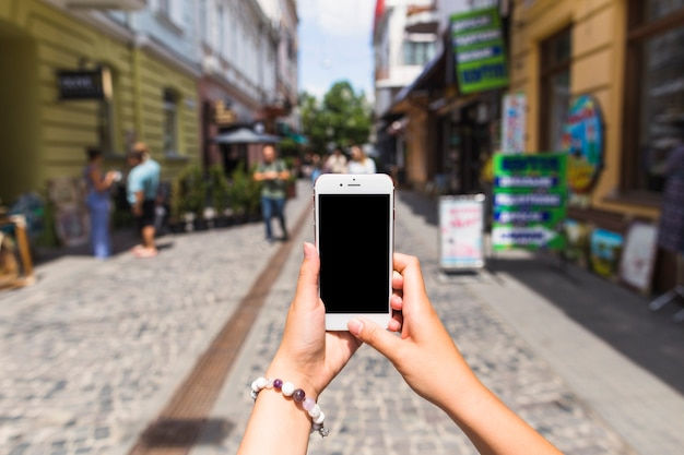 Die hand der frau, die foto auf mobiltelefon an der straße macht Kostenlose Fotos