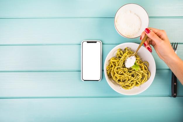 Die hand der frau, die gewürz auf spaghettis hinzufügt Kostenlose Fotos