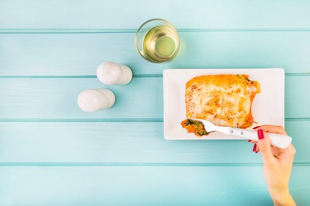 Die hand der frau, die lasagne auf hölzernem hintergrund isst Kostenlose Fotos