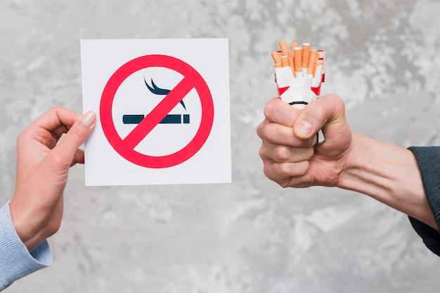 Die hand der frau, die nichtraucherzeichen nahe der hand des mannes hält päckchen zigaretten hält Kostenlose Fotos