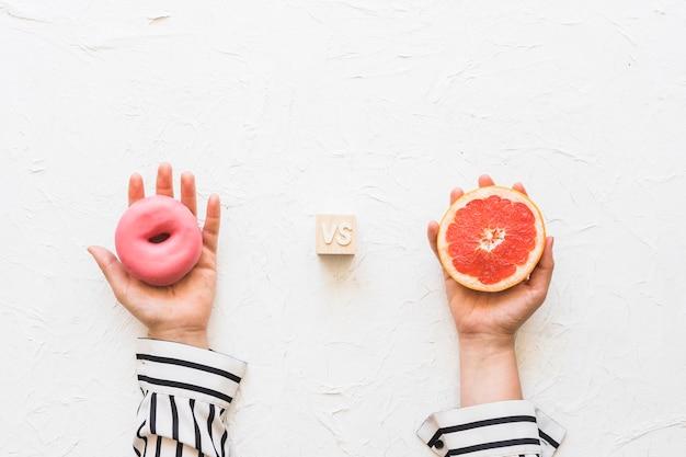 Die hand der frau, die rosa donut gegen pampelmusescheibe über strukturiertem hintergrund hält Kostenlose Fotos