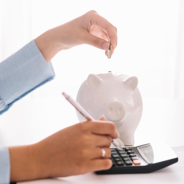 Die hand der frau, die taschenrechner beim einstecken der münze in piggybank verwendet Premium Fotos
