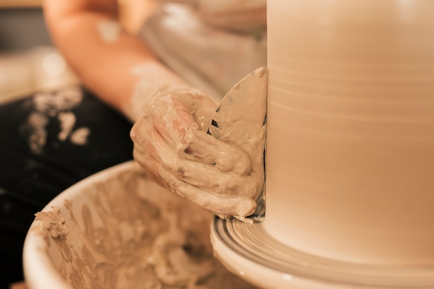 Die hand der frau, die vase mit flachem werkzeug auf töpferscheibe glatt macht Kostenlose Fotos