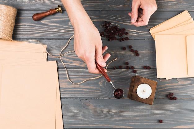 Die hand der frau, die wachsrolle mit handwerksmaterial über hölzernem schreibtisch hält Kostenlose Fotos