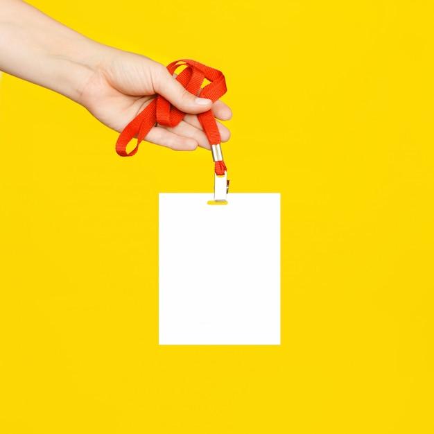 Die hand der frau hält ein sauberes weißes abzeichen an einer roten schnur an einer leuchtend gelben wand. Premium Fotos