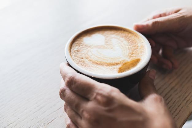 Die hand der frau hält eine heiße cappuccinokaffeetasse auf einer braunen hölzernen tabelle Premium Fotos