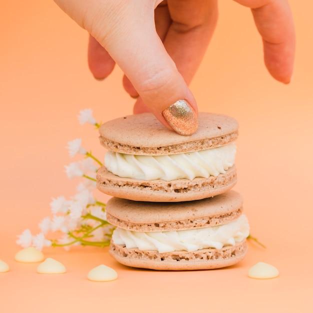 Die hand der frau mit dem goldenen nagellack, der makrone gegen farbigen hintergrund nimmt Kostenlose Fotos