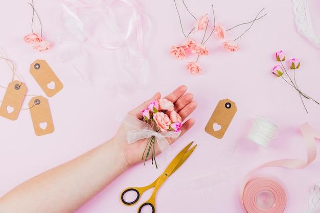 Die hand der frau, welche die künstlichen blumen mit band auf rosa hintergrund zeigt Kostenlose Fotos