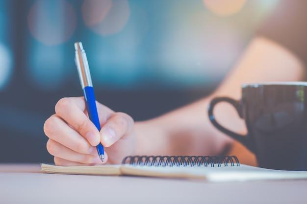 Die hand der geschäftsfrau schreibt auf ein notizbuch mit einem stift. Premium Fotos