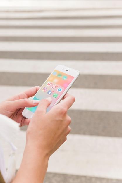 Die hand der person, die mobiltelefon mit social media-mitteilungen auf schirm hält Kostenlose Fotos