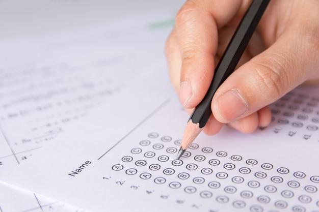 Die hand der studenten, die bleistiftschreiben vorgewählte wahl auf antwortblättern und mathematikfrageblättern hält. studenten testen bei der prüfung. schulprüfung Premium Fotos