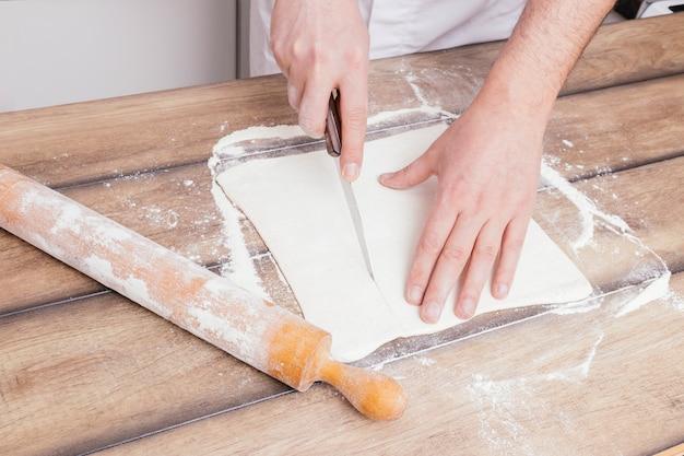 Die hand des bäckers, die den teig mit scharfem messer auf holztisch schneidet Kostenlose Fotos