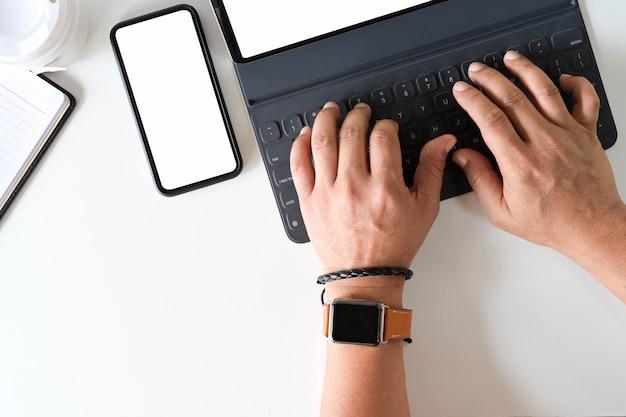 Die hand des draufsichtfreiberuflers unter verwendung auf tastaturtablette auf schreibtischarbeitsplatz. Premium Fotos