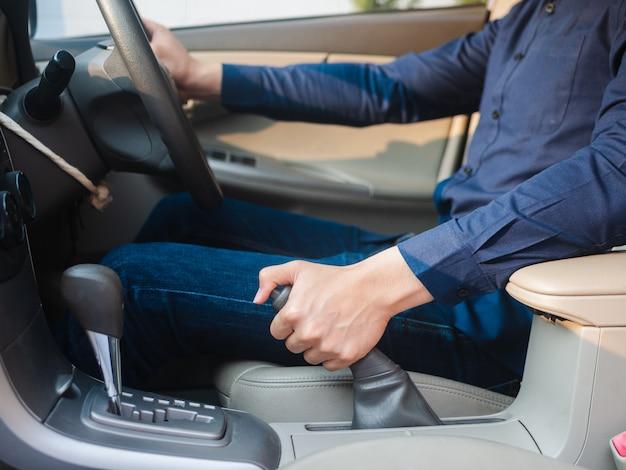 Die hand des fahrers, die die handbremse in einem auto zieht Premium Fotos