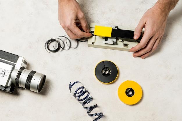 Die hand des fotografen schneidet einen filmstreifen auf konkretem hintergrund Kostenlose Fotos