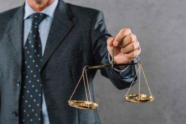 Die hand des männlichen anwalts, die gerechtigkeitskala gegen grauen strukturierten hintergrund zeigt Kostenlose Fotos