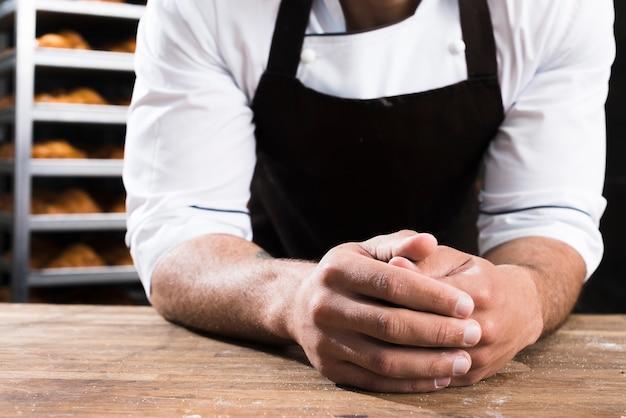 Die hand des männlichen bäckers, die auf holztisch sich lehnt Kostenlose Fotos