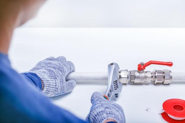 Die hand des männlichen klempners, die abflussrohr-leckage mit verstellbarem schlüssel repariert. Premium Fotos