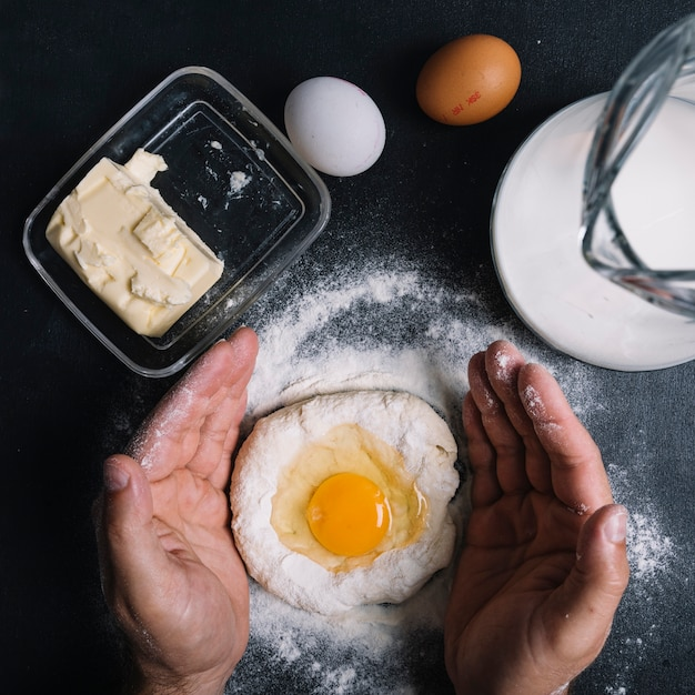 Die hand des mannes, die ei york über dem teig auf küchenarbeitsplatte bedeckt Kostenlose Fotos