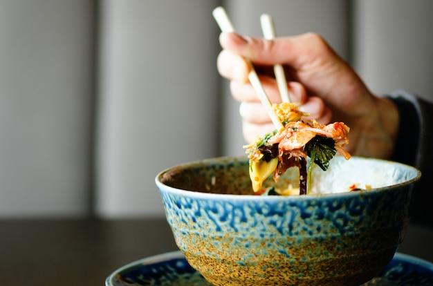Die hand des mannes, die essstäbchen über einer platte der japanischen, thailändischen, chinesischen mahlzeit - reis, pilz, gemüse hält. Premium Fotos