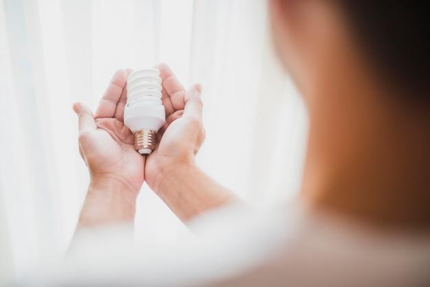 Die hand des mannes, die kompakte leuchtstoff glühlampe hält Kostenlose Fotos