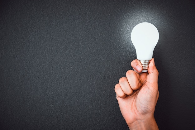 Die hand des mannes, die led-glühlampe über schwarzer wand hält Premium Fotos