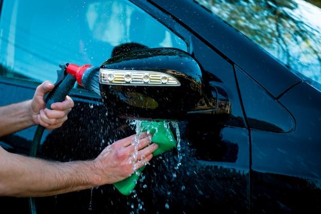 Die hand des mannes, die vom schwarzen auto durch schwamm und eine andere handhand poliert, hält den schlauch für das waschen im freien. Premium Fotos