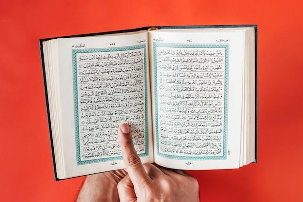 Die hand des mannes hält den geöffneten koran und zeigt mit dem finger auf einen einfachen burgunderfarbenen raum. Premium Fotos