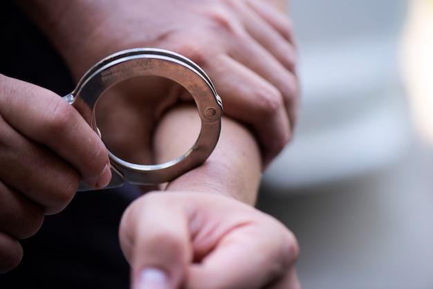 Die hand des mannes ist mit den handschellen verriegelt Premium Fotos