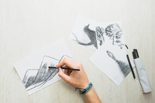 Die hand des menschen, die auf papier mit holzkohlenstock nahe schöner hand gezeichneter zeichnung skizziert Kostenlose Fotos