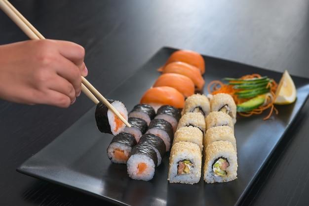 Die hand des menschen nimmt eine rolle, eine von den sushi, die auf einer schwarzen rechteckigen platte eingestellt werden, mit in essig eingelegtem ingwer und essstäbchen, holztischhintergrund, selektiver fokus. japanisches essen thema Premium Fotos