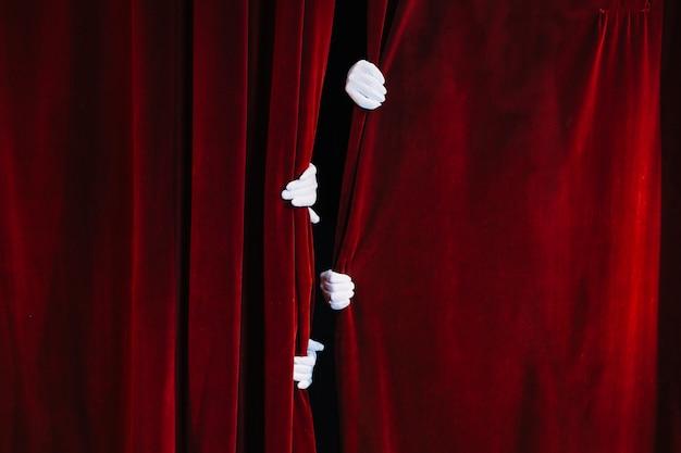 Die hand des pantomimen, die geschlossenen roten vorhang hält Kostenlose Fotos