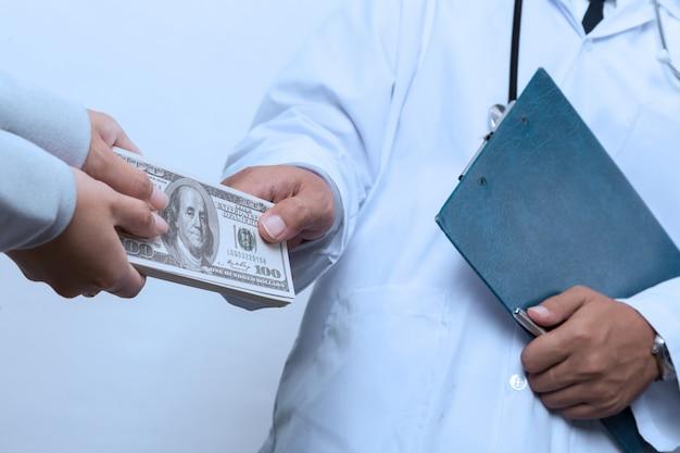 Die hand des patienten, die dem doktor ein geld zahlt Premium Fotos