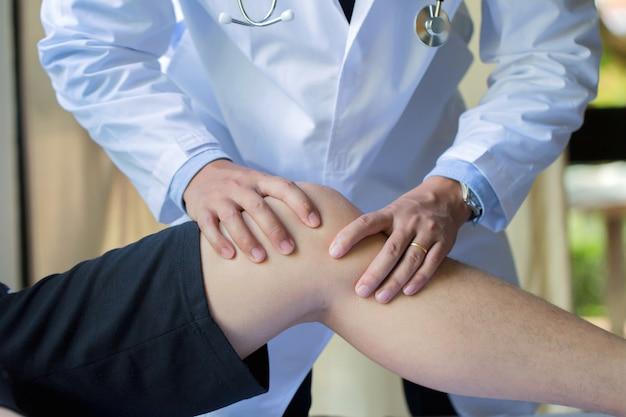 Die hand des physiotherapeuten, die dem männlichen patienten in der klinik knie-übung gibt Premium Fotos