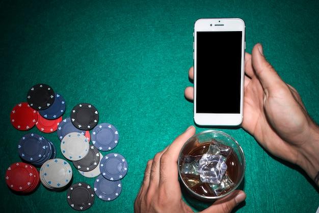 Die hand des pokerspielers, die handy zeigt und whiskyglas auf schürhakentabelle hält Kostenlose Fotos