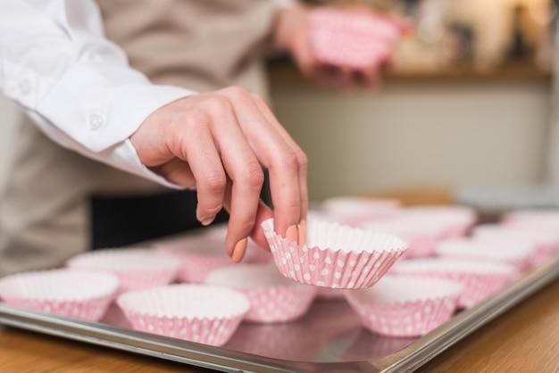 Die hand des weiblichen bäckers, die den kasten des kleinen kuchens auf das fach setzt Kostenlose Fotos