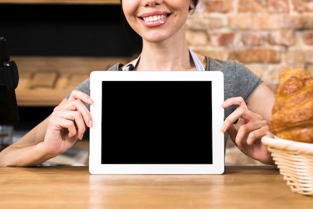Die hand des weiblichen bäckers, die digitale tablette des leeren bildschirms auf tabelle zeigt Kostenlose Fotos