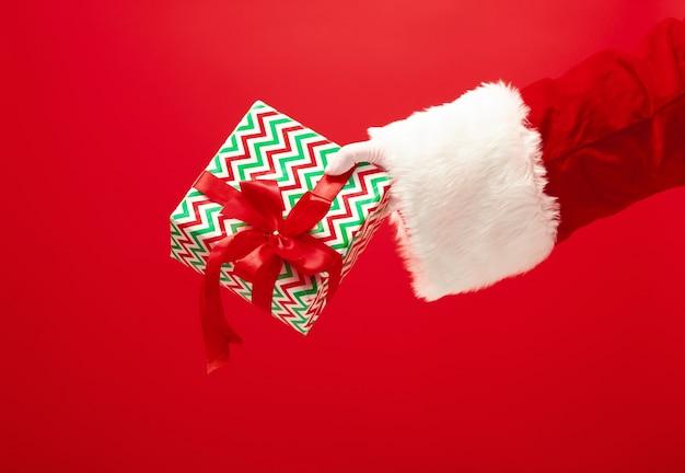 Die hand des weihnachtsmannes, der ein geschenk auf rot hält Kostenlose Fotos