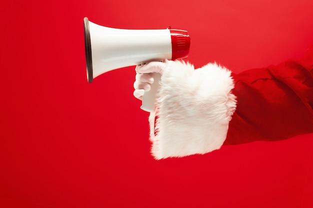 Die hand des weihnachtsmannes hält ein megaphon auf rot Kostenlose Fotos